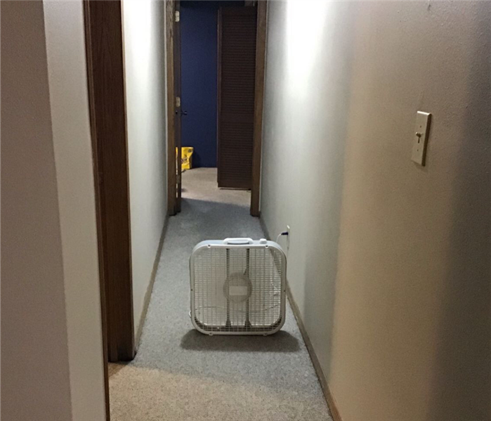 A hallway with white walls on each side and one white box fan in the middle of the hallway.