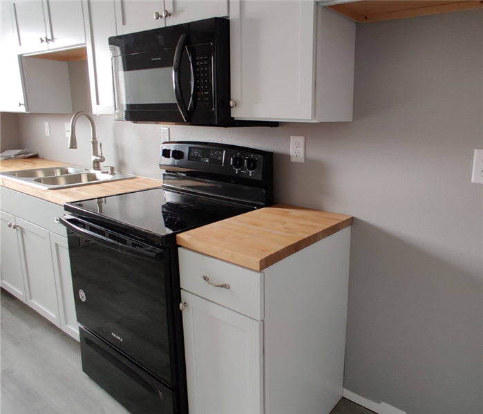 A clean and repaired kitchen with new appliances.